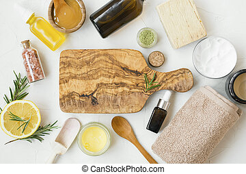 Natural skincare cosmetics products with oils, clay, manuka honey, lemon, rosemary, bath salt , soap, salve balm with wooden board