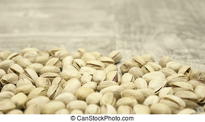 Natural Pistachios on wooden background in studio. Healthy...