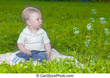 Natural Portrait of Little Cute Caucasian Toddler Child Sitting on Grass Outdoors.