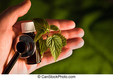 A bottle with nettle on the palm of your hand
