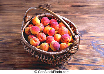 Natural ripe apricots in a wicker basket on a natural wooden background, close up