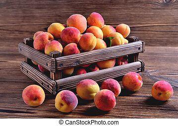 Natural ripe fresh apricots in a wooden crate on a natural wooden background