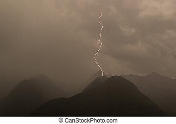 single lightning bolt strike in mountain peak gray sky