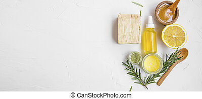 Natural skincare ingredients with manuka honey, lemon, essential oil, clay, balm, rosemary herbs and natural soap with copy space