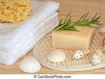 Natural skincare cleansing products products consisting of white hand towels, sponges, soap with fresh rosemary herb and shells. Over bamboo background.