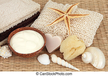 Natural skincare products of moisturising cream, exfoliating scrub, soap, sponge, towels and sea shells.