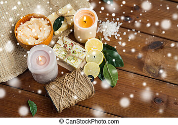 natural soap and body scrub with candles on wood