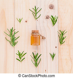 Natural Spa Ingredients rosemary essential oil for aromatherapy with circle of rosemary  leaf on wooden background.