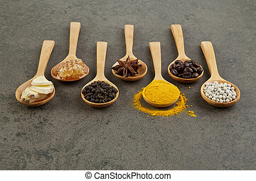Natural Spa Ingredients.Variety herbal on rustic background from top view, coffee beans, pepper, turmeric, ginger, honey, anise in wooden spoon
