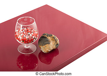Natural stone and a glass on the varnished coating, the reflection of objects.
