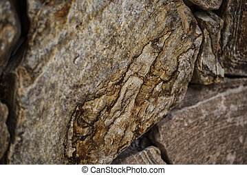 Natural stone of brown color, a piece of a wall from a natural stone. Background of natural stone.