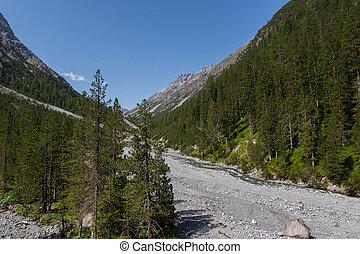 natural Welschtobel valley near Arosa in sunlight, forest, debris, blue sky