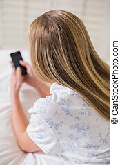 Natural woman lying on bed using smartphone