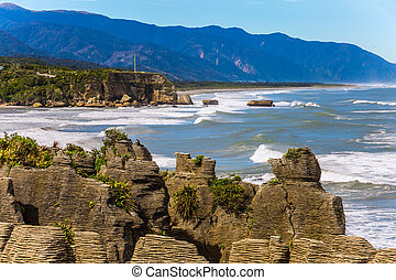 """Pancake Rock is a natural wonder of New Zealand. Incredible journey to the ends of the world. Stone """"pancakes"""", stacked on top of each other. The concept of ecological, active and photo tourism"""