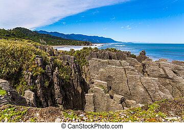 """Pancakes Rock is a natural wonder of New Zealand, Paparoa National Park. Stone flat """"pancakes"""", stacked on top of each other. Travel to New Zealand. The concept of ecological, active and photo tourism"""