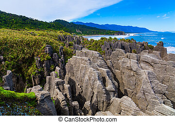 """Paparoa National Park. Stone flat """"pancakes"""", stacked on top of each other. Magic islands in the ocean. Pancakes Rock is a natural wonder of New Zealand. The concept of ecological, active and photo tourism"""