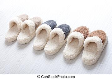 Three pair of natural woollen slippers on wooden floor