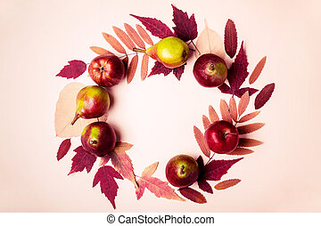 Natural wreath of dry pink leaves and pears on pink background. Autumn harvest concept.