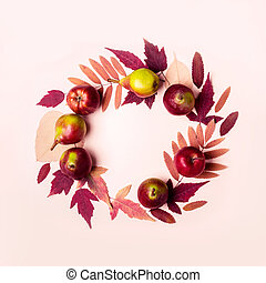 Natural wreath of dry pink leaves and pears on pink background. Autumn harvest concept