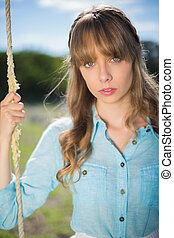 Natural young woman sitting on swing