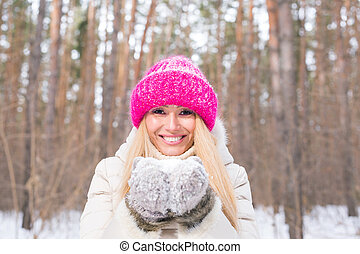 Nature and people concept - Close up portrait of attractive woman dressed in pink hat in winter park. Woman holding snow in her hands