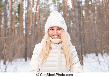 Nature and people concept - Close up portrait of attractive woman dressed in white hat in winter nature