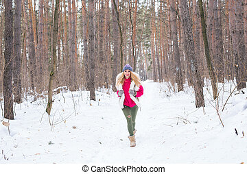 Nature and people concept - Portrait of running young blond woman in the winter park