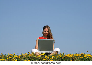 Casual woman working with laptop in a flowering dandelion field.