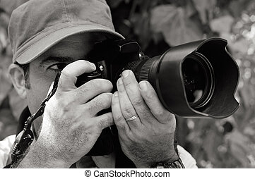 Nature and Wildlife Photographer looks through a camera ...