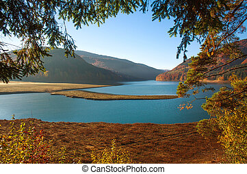 Nature background, lake in mountains covered with autumn forest