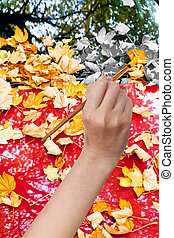 paintbrush paints yellow autumn leaves on red car