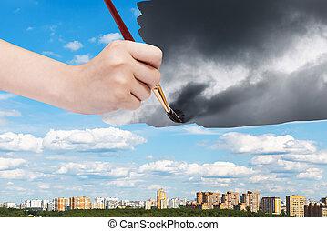paintbrush paints storm clouds over sunny city