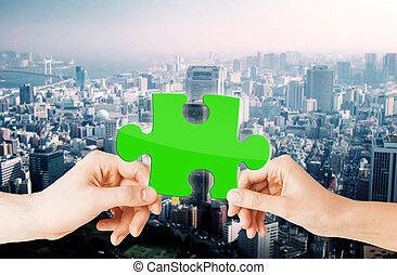 hands with green puzzle over city background