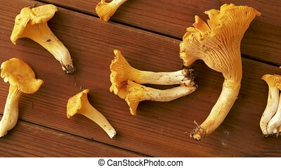 chanterelles on wooden background - nature, environment and...