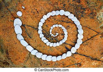 Nature Harmony - Spiral of pebbles on the sea boulder
