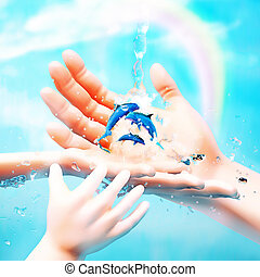 Nature in human hand. The concept of environmental protection. Design with hands, ocean, dolphins, water jets and rainbow.