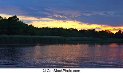 Nature landscape of a sunset, red and pink cloudy sky, on a lake
