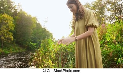 nature, occult science and supernatural concept - young woman or witch performing magic ritual on river and touching water