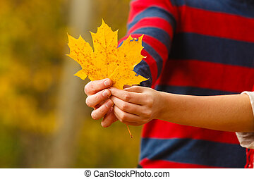 Young person holding leaf.