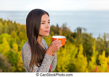 Nature outdoors coffee drinking woman relaxing in forest autumn sunshine enjoying her morning coffee. Happy multiracial canadian Asian Chinese / Caucasian girl in her 20s, Canada