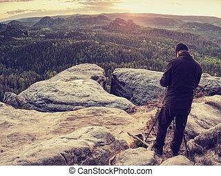 Nature photographer hold tripod with camera. Man at sunrise