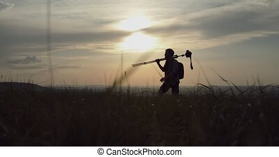 Nature photographer in silhouette walking with tripod - ...