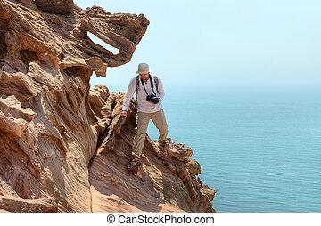 Nature photographer scrambles on rock while traveling, Hormuz Island,  Iran.