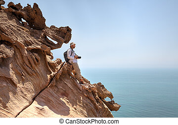 Nature photographer standing on edge of cliff above the sea.