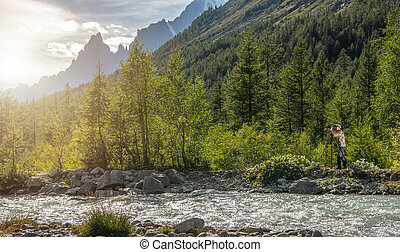 Nature Photographer Taking Pictures Next to Scenic Mountain River
