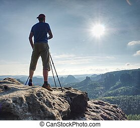 Nature photographer working with camera and tripod on view