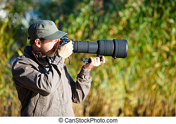 Nature photographer - Young nature photographer with taking...
