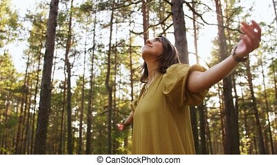 woman or witch performing magic ritual in forest - nature, ...