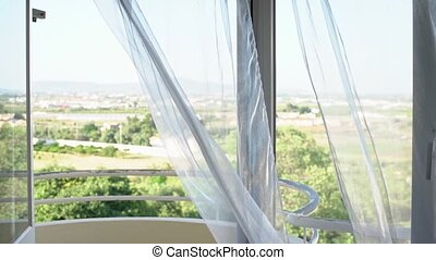 Nature view, landscape through the window. Light wind sways tulle. High key. Overexposure