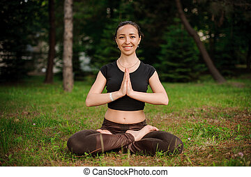 Nature yoga session in beautiful green woods, between trees. Meditation - namaste in lotus pose.